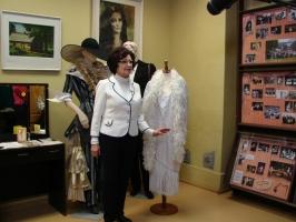 Olga Dreģe pie saviem teātra tērpiem, kas glabājas muzeja krātuvē Sarkaņos.